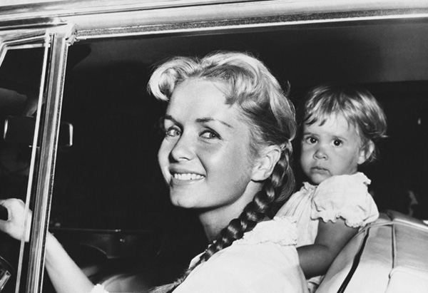 """Actress Debbie Reynolds, accompanied by her daughter, Carrie, 2, leaves her home to spend the rest of the day with a girlfriend whom she did not identify, Sept. 10, 1958 in Los Angeles. She said she was leaving """"to get away from it all,"""" a reference to the hullabaloo raised over the dating by her husband, Eddie Fisher, of actress Elizabeth Taylor in New York. (AP Photo)"""